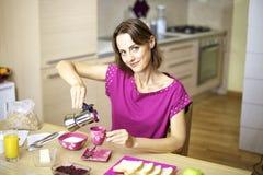 Mulher nos pijamas que derramam o café na cozinha Fotografia de Stock