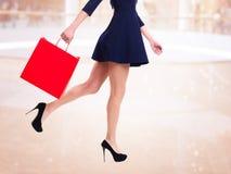 Mulher nos saltos altos com saco de compras vermelho.