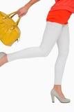 Mulher nos saltos altos que apressam-se com saco amarelo Fotografia de Stock