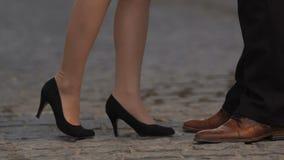 Mulher nos saltos altos que aproximam e que beijam o noivo, exterior, close up dos pés filme