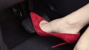 A mulher nos saltos altos vermelhos calça a pressão de pedais do carro filme