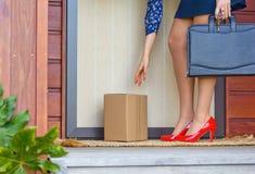 A mulher nos saltos vermelhos recolhe o pacote na porta da rua da casa Fotos de Stock Royalty Free