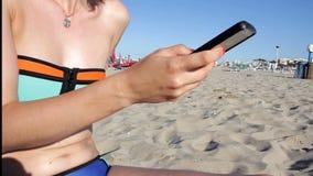 Mulher nos sms do biquini que texting usando o app no telefone esperto na praia Close up das mãos usando o smartphone fora móvel vídeos de arquivo