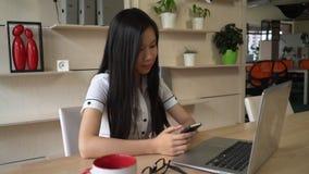 Mulher nos sms texting do escritório no smartphone filme