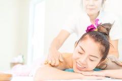 Mulher nos termas com sorriso ao retirar a massagem pelo terapeuta dos termas Fotos de Stock