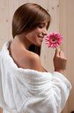 A mulher nos termas ou a sauna relaxam o centro com flor Fotos de Stock Royalty Free