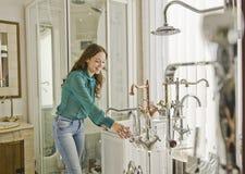Mulher nos torneiras e na loja do encanamento Fotos de Stock Royalty Free