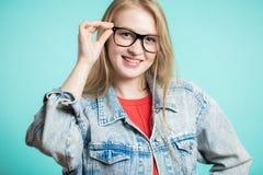 A mulher nos vidros em um fundo azul olha a câmera com um sorriso Imagens de Stock Royalty Free