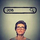 Mulher nos vidros que pensa procurando um trabalho novo isolada no fundo cinzento da parede Imagens de Stock