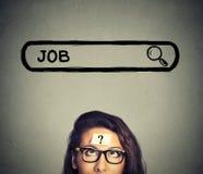 Mulher nos vidros que pensa procurando um trabalho novo isolada no fundo cinzento da parede Imagens de Stock Royalty Free