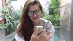 Mulher nos vidros que sorri e que usa o smartphone perto da associação no país tropical video estoque