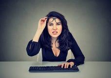 A mulher nos vidros que usam o computador tem problemas da visão fotografia de stock