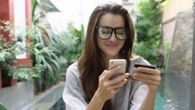 A mulher nos vidros usa a operação bancária em linha no smartphone com o cartão de crédito perto da associação no país tropical vídeos de arquivo