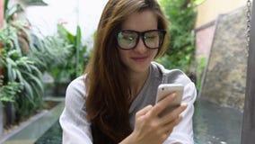 Mulher nos vidros usando o smartphone perto da associação no país tropical video estoque