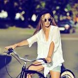 Mulher nova à moda do moderno em uma bicicleta retro Forma ao ar livre Imagens de Stock