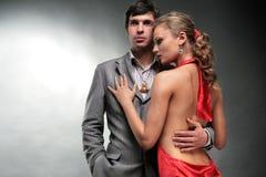 A mulher nova abraça o homem. Mulher em um vestido vermelho. Fotos de Stock Royalty Free