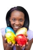 Mulher nova africana que mostra ovos de Easter coloridos Foto de Stock Royalty Free