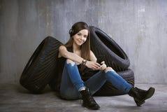 Mulher nova, alegre com os fones de ouvido que sentam-se perto dos pneus e Imagem de Stock