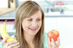 Mulher nova alegre que prende um appke e uma banana Fotografia de Stock Royalty Free
