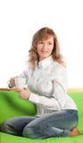 Mulher nova alegre que senta-se no sofá Fotos de Stock Royalty Free