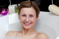 Mulher nova alegre que tem um banho Imagens de Stock Royalty Free