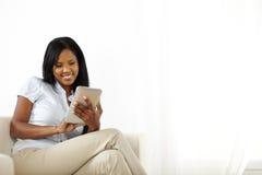 Mulher nova alegre que usa um PC da tabuleta Fotos de Stock