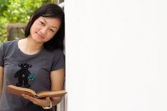 Mulher nova asiática com o livro aberto na mão foto de stock royalty free