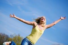 Mulher nova ativa que salta altamente na luz do sol imagem de stock