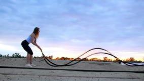 A mulher nova, atlética, loura, executa exercícios da força com a ajuda de uma corda grossa, desportiva No alvorecer, no arenoso vídeos de arquivo