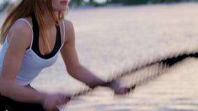 A mulher nova, atlética, loura, executa exercícios da força com a ajuda de uma corda grossa, desportiva No alvorecer, no arenoso filme