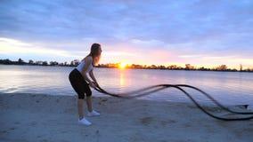 A mulher nova, atlética, loura, executa exercícios da força com a ajuda de uma corda grossa, desportiva No alvorecer, no arenoso video estoque