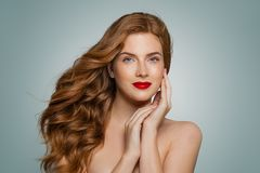 Mulher nova atrativa à moda do ruivo que olha a câmera no fundo azul imagem de stock royalty free