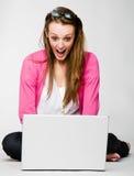 Mulher nova atrativa choc por seu portátil imagem de stock