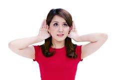 Mulher nova atrativa com mãos atrás de suas orelhas fotografia de stock royalty free