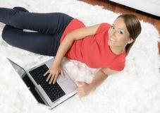 Mulher nova atrativa com um computador imagens de stock royalty free