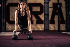 Mulher nova atrativa da aptidão do gym que faz impulso-UPS foto de stock
