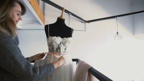 Mulher nova atrativa do desenhador de moda que trabalha em casa o estúdio Alfaiate Makes Wedding Dress filme