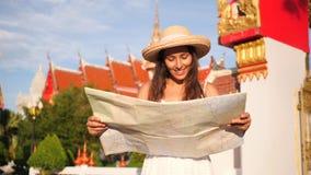 Mulher nova atrativa do moderno do turista da raça misturada no vestido branco e em Straw Hat grande com o mapa da cidade que olh vídeos de arquivo
