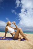Mulher nova atrativa que bebe na praia Imagem de Stock