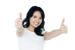 A mulher nova atrativa que dá os polegares levanta o sinal Fotos de Stock