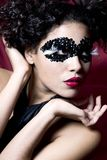 Mulher nova atrativa que desgasta uma máscara preta da gema Fotografia de Stock