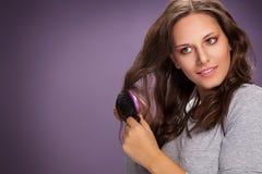 Mulher nova atrativa que escova seu cabelo fotos de stock
