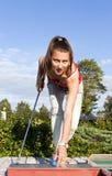 Mulher nova atrativa que põr a esfera de golfe sobre o verde Imagens de Stock