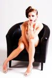 Mulher nova atrativa que senta-se em uma cadeira Fotografia de Stock Royalty Free