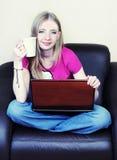 Mulher nova atrativa que usa o portátil em casa Foto de Stock