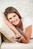 Mulher nova atrativa que wathing a tevê fotografia de stock royalty free