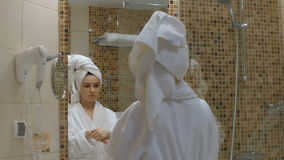 A mulher nova, bonita aplica o creme de cara no banheiro video estoque
