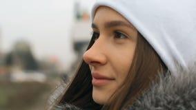 A mulher nova, bonita, atrativa em um revestimento à moda anda através das ruas da cidade Ri, levanta para a câmera filme