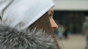 A mulher nova, bonita, atrativa em um revestimento à moda anda através das ruas da cidade Ri, levanta para a câmera video estoque