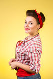 Mulher nova bonita com composição do pino-acima e penteado que levanta sobre o fundo cor-de-rosa Foto de Stock